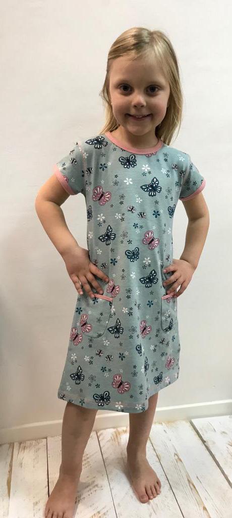 niña posando con vestido azul con flores y mariposas
